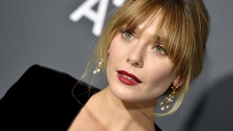 A zoomed in shot of Elizabeth Olsen wearing red lipstick, a black dress and gold earrings