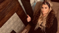 Jessica Simpson pregnant and lounging on a couch giving a thumbs up