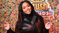 Jordyn Woods posing in front of a wall covered in candy
