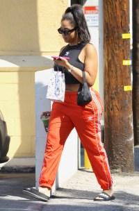 Jordyn Woods wearing a black shirt and orange pants walking in Studio City, CA
