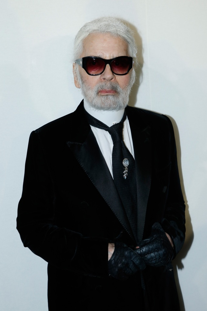 Karl Lagerfeld wearing a black suit, black sunglasses and white ponytail