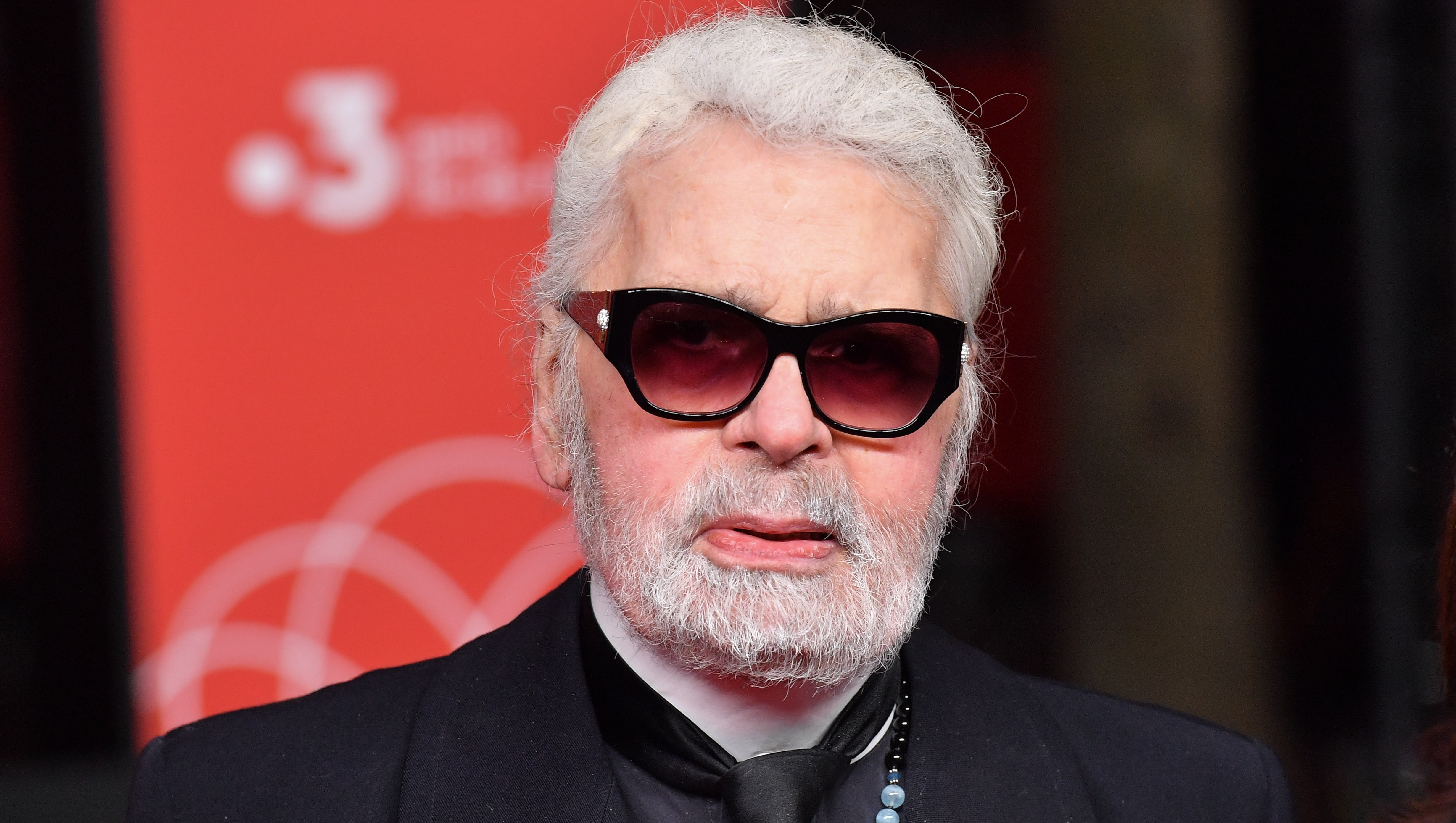 Karl Lagerfeld wearing black sunglasses and a black blazer
