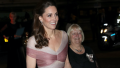 Kate Middleton smiling in a pink gown while out in London