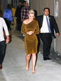Katy Perry wearing a tight, gold dress with black sunglasses