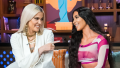 Khloe Kardashian and Kim Kardashian smiling and sitting on a coach