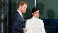 Prince Harry wearing a navy suit with his hand on Meghan Markle's back as she wears a white dress and jacket