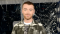 Sam Smith smiling wearing a patterned green jacket