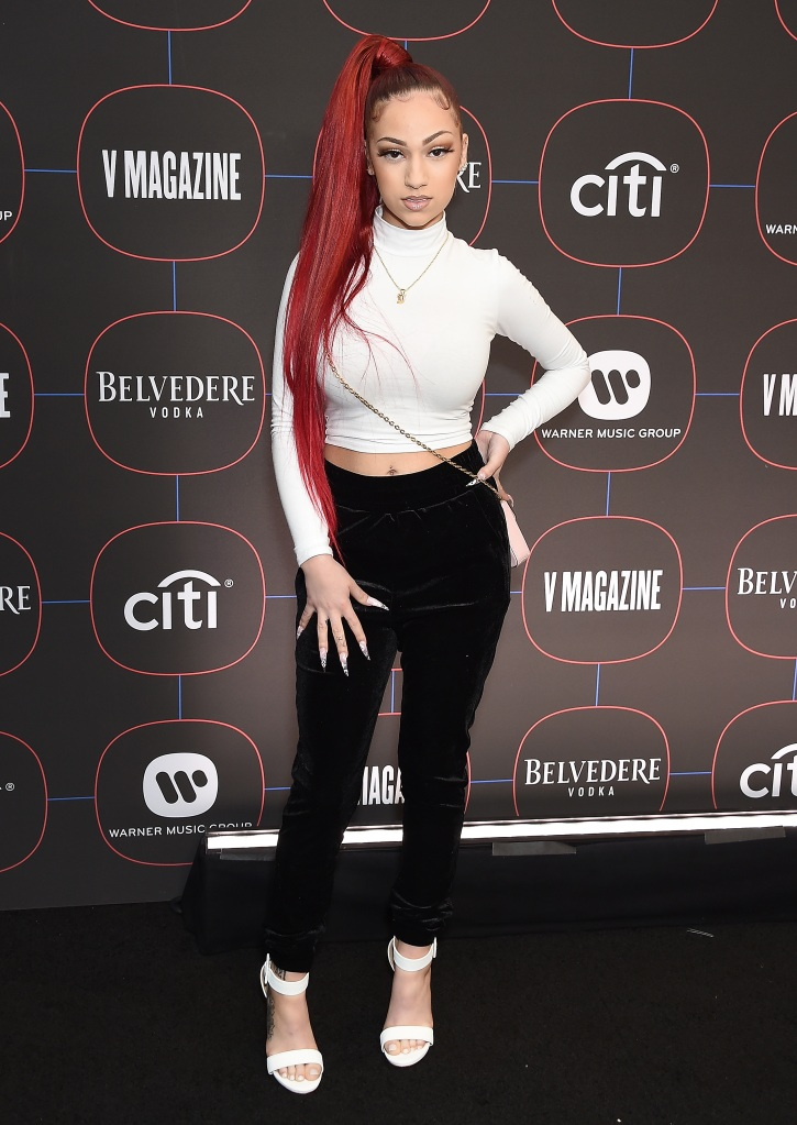 Bhad Bhabie posing in a white top and black pants