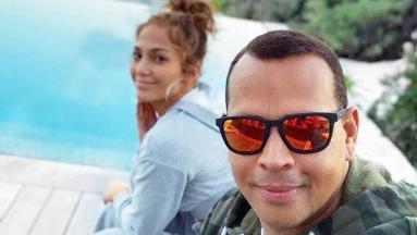 Alex Rodriguez and Jennifer Lopez taking a selfie next to a pool.