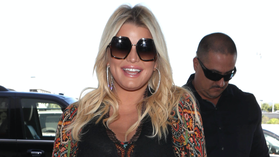 Jessica Simpson smiling and wearing black sunglasses.