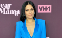 Jessie J posing and wearing a blue suit.