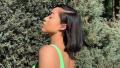 Jordyn Woods posing in a lime green bikini with short, black hair.