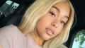 Jordyn Woods with blonde hair taking a selfie in a car.