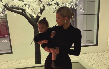 Kylie Jenner holding Stormi Webster while they both wear matching black dresses