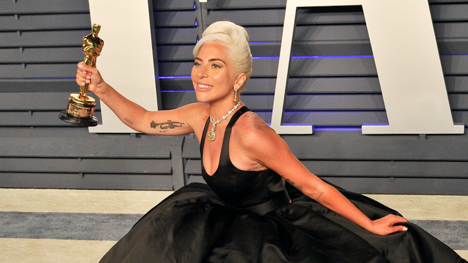 Lady Gaga kneeling on the red carpet with her Oscar trophy in hand