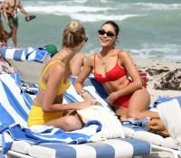 Olivia Culpo wears a red bikini as she hits the beach with model Devon Windsor in Miami