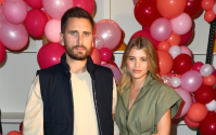 Scott Disick posing in front of balloons with Sofia Richie.