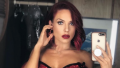 Sharna Burgess posing in a mirror selfie wearing a red shiny outfit