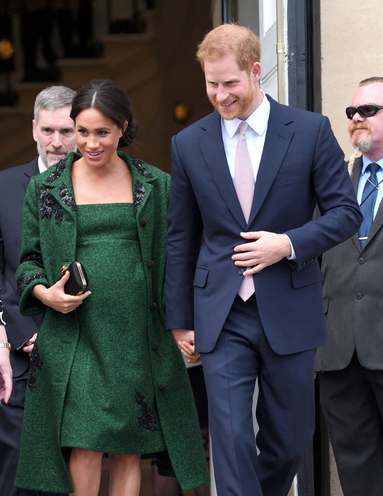 Meghan Markle wears green dress and coat with her hair up and Prince Harry holds her hand in a blue suit
