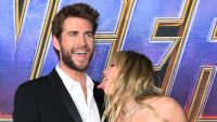 Miley Cyrus licks Liam Hemsworth red carpet avengers black dress