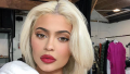 Kylie Jenner posing for a selfie with blonde hair and red lipstick.
