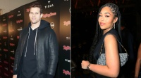 Kris Humphries in leather jacket and hoodie and Jordyn Woods wearing black dress and dior bag
