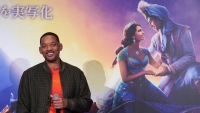 Will Smith Wearing an Orange Shirt In Front of Aladdin Sign