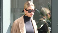 Hailey Baldwin street style black crop top sunglasses tan coat low bun