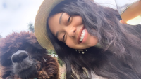 Jordyn Woods hat llama glass of wine smiling