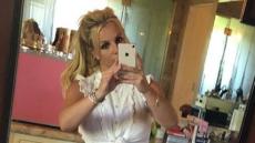 Britney Spears taking a mirror selfie in a white top