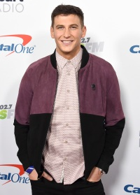 Bachelor Star Blake Horstmann Smiles on Capital One Red Carpet in Pink Button Down Shirt With Purple and Black Bomber Jacket