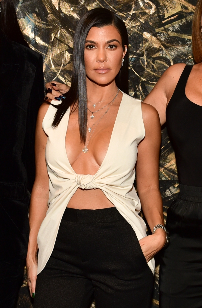 Kourtney Kardashian Stands in a White Shirt That Shows Her Breasts and Black Pants
