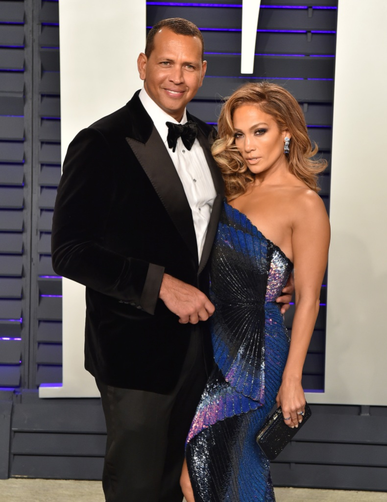 Jennifer Lopez Poses in a Blue Sparkly Strapless Dress With Big Earring and Voluminous Hair With Alex Rodriguez Wearing a Black Tux With Black Bow Tie During the 2019 Vanity Fair Oscars After Party