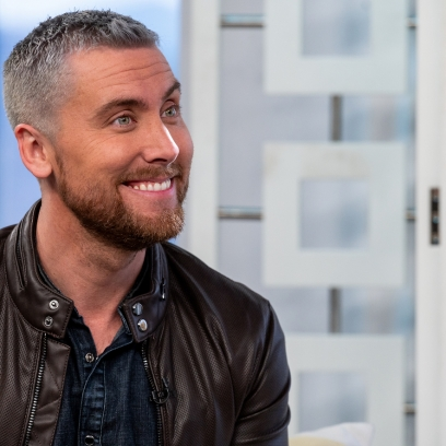 Lance Bass Smiles With Grey Hair and Red Beard in Leather Jacket