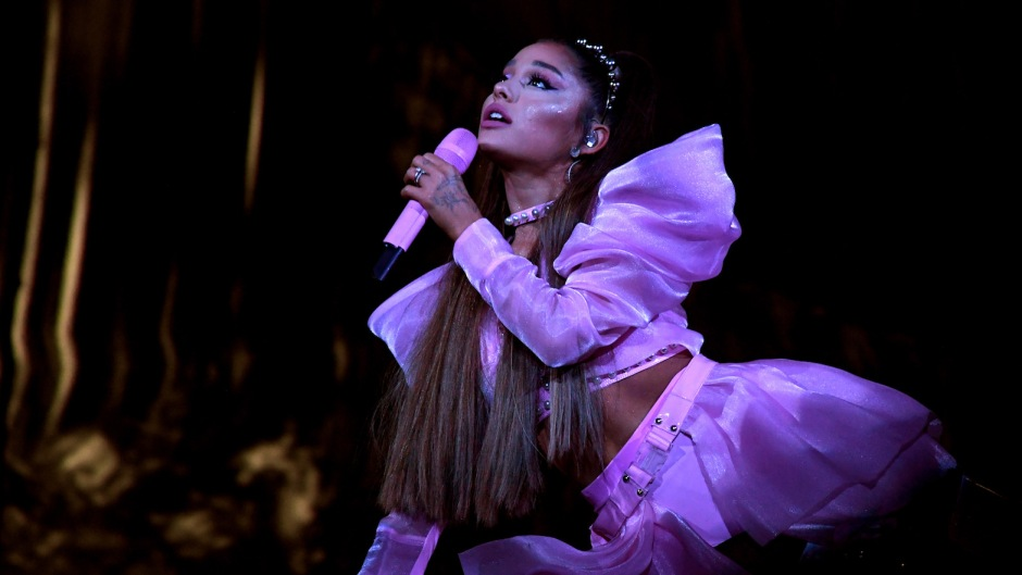 Ariana Grande Lays on Stage During Sweetener World Tour in a Pink Crop Top and Skirt Holding a Pink Microphone