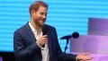 Prince Harry Shrugs and Smiles in Navy Blue Blazer With White Button Down Shirt While Holding a Microphone