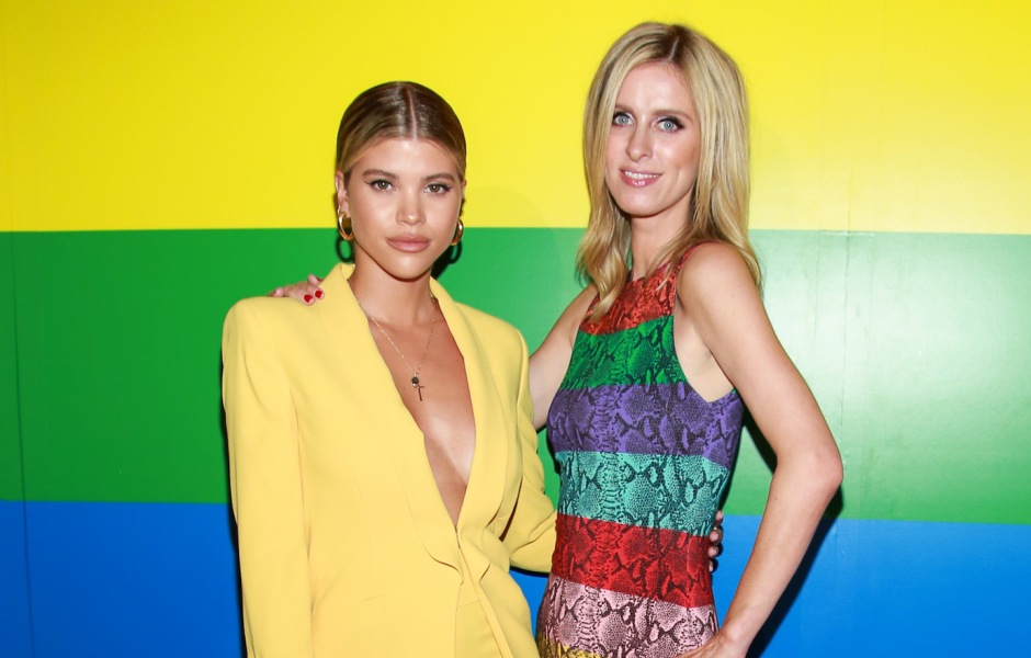 Sofia Richie in a Yellow Pantsuit Stands With Nicky Hilton in a Rainbow Dress Against a Rainbow Wall