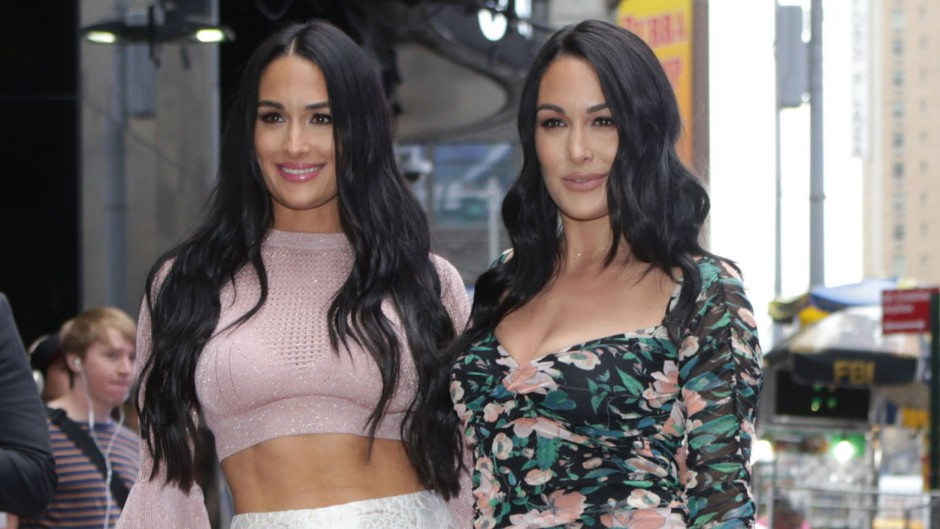 Nikki Bella in a Pink Crop Top and White Lace Pants and Brie Bella in a Flowered Dress Stand Together in New York City