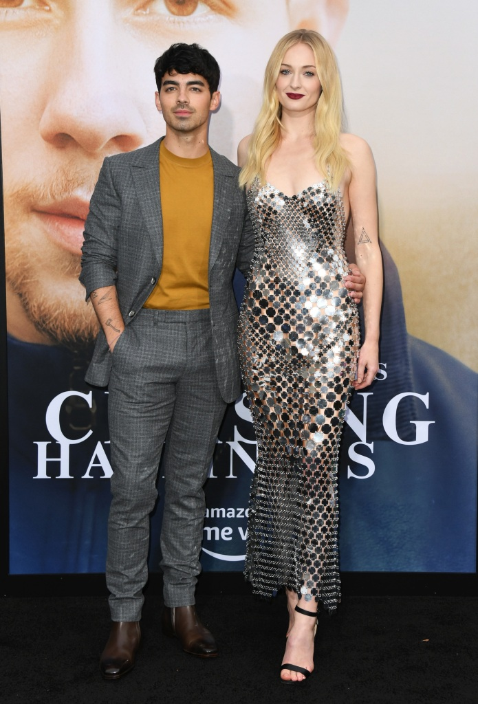 Sophie Turner Wears Mirrored Strapless Gown and Ruby Red Lip Standing With Joe Jonas in a Mustard Yellow Sweater and Grey Suit