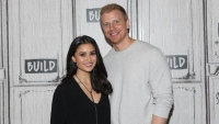 Catherine Lowe in a Black Top Stands With Husband Sean Lowe Wearing a White Sweater Pregnant With Baby No. 3