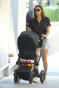 Irina Shayk in a Black Top and Jean Shorts With a Black Stroller