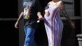 Pregnant Amber Rose cradles her baby bump while wearing a striped summer dress