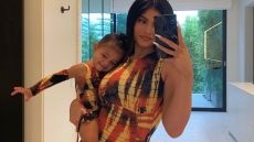 Kylie Jenner and daughter Stormi Webster wearing matching dresses and taking a mirror selfie