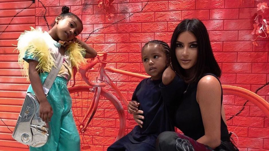 Kim Kardashian North West and Saint West in Japan Posing Against a Red Wall