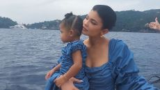 Kylie Jenner and Stormi Webster matching blue ruffle dresses on a boat in italy