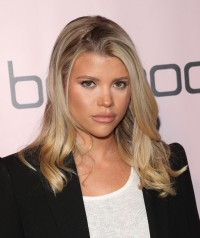 Sofia Richie Looks at the Camera With Wavy blonde Hair White Shirt and Black Blazer