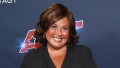 Abby Lee Miller smiling with short brown hair and a black blouse