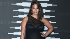 A pregnant Ashley Graham posing in a black dress