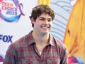 Noah Centineo smiling and wearing a flannel at the 2019 Teen Choice Awards
