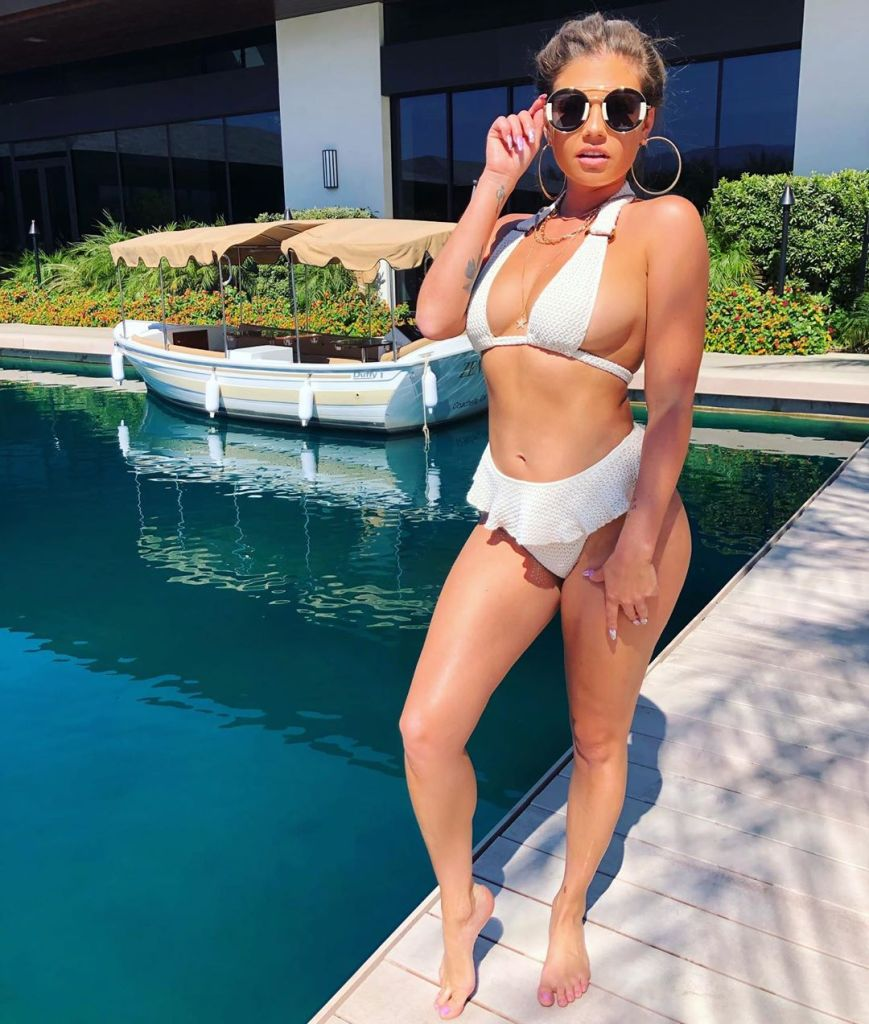Chanel West coast in a white bikini and gold accessories